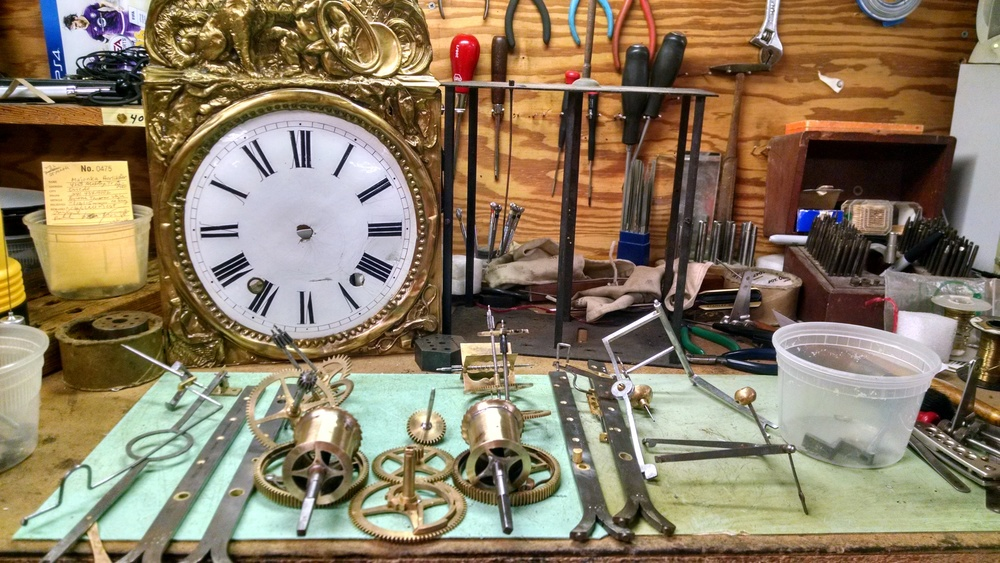 This is the clock on the bench before assembly. You can see all the gears, dial, movement plates and movement case.
