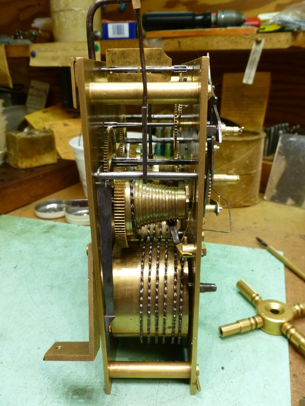 There is a large mainspring in the barrel on the bottom. To wind the clock, you wind the chain onto the cone in the middle of the movement. The theory behind the cone is that when the clock is nearing the end of the weak and the mainspring is running out of power, it provides the same amount of power to the mechanism using an adjusting ratio.