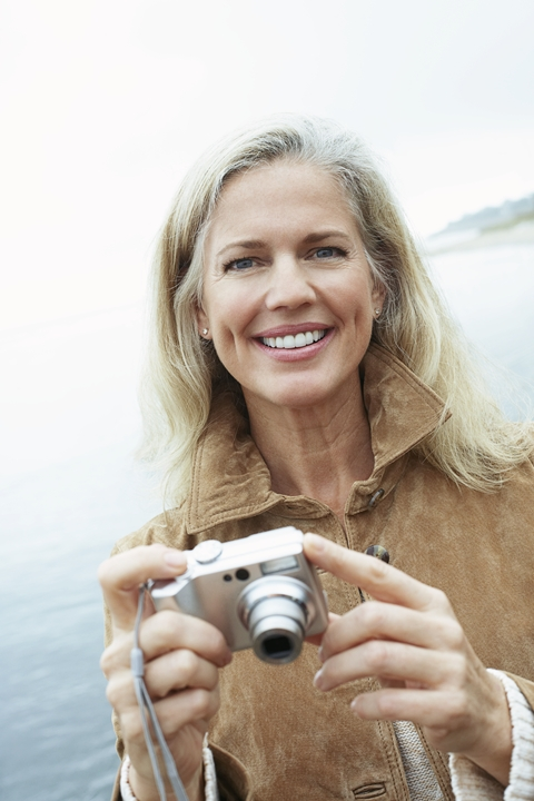 Attractive older woman holding camera smiling with dental implant