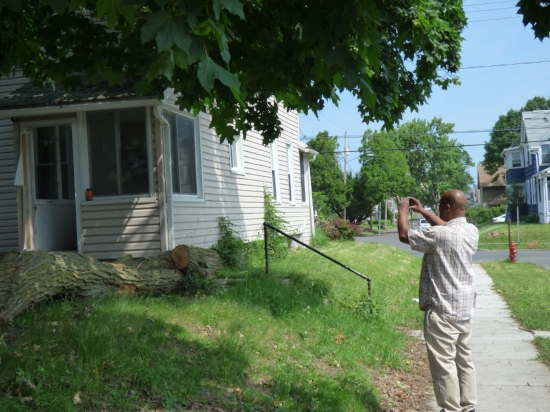 An inspector documenting the status of an overgrowth violation.
