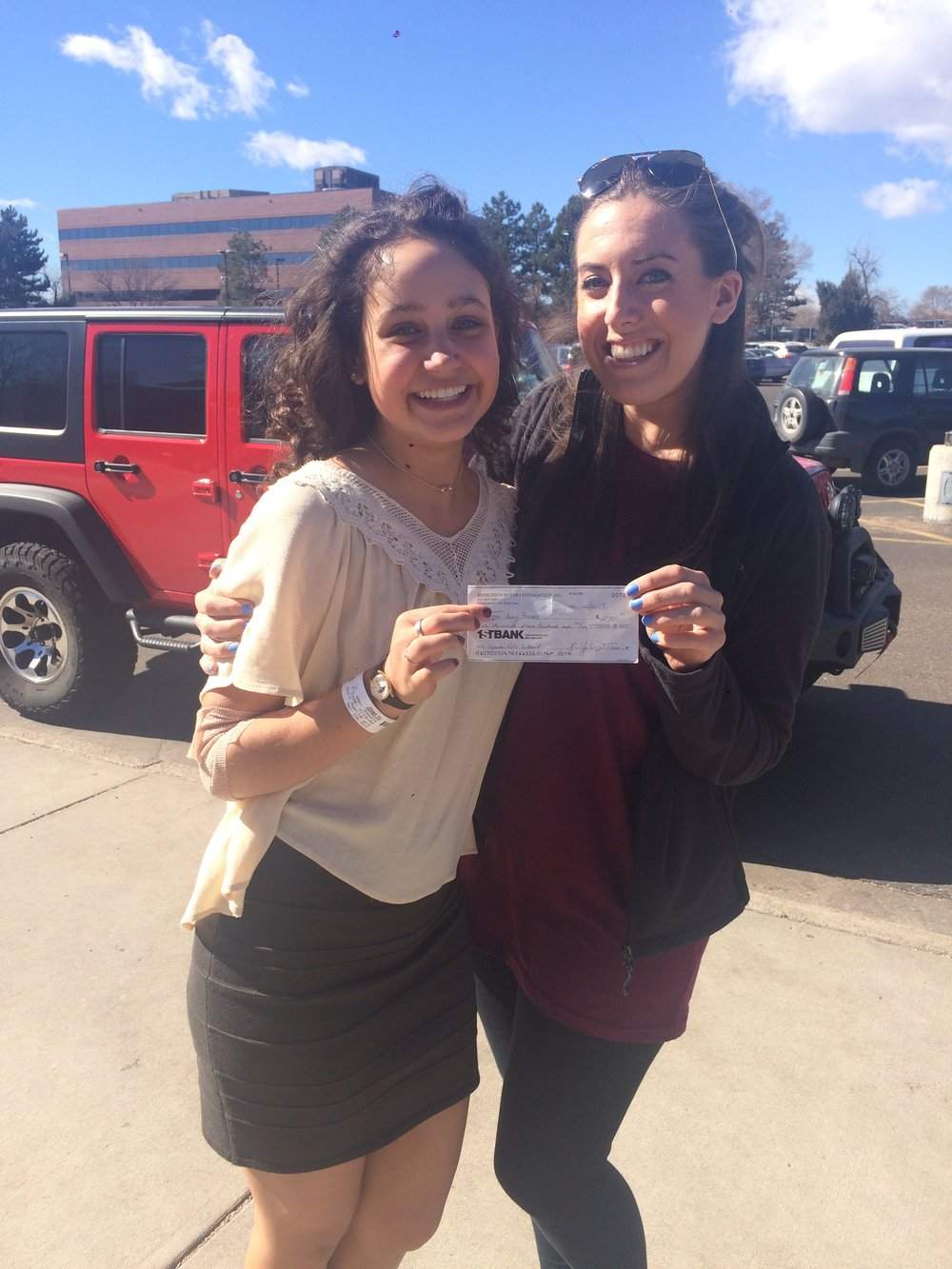 Zoi Johns (left) presenting her final check to our Executive Director, Jayme Ward.