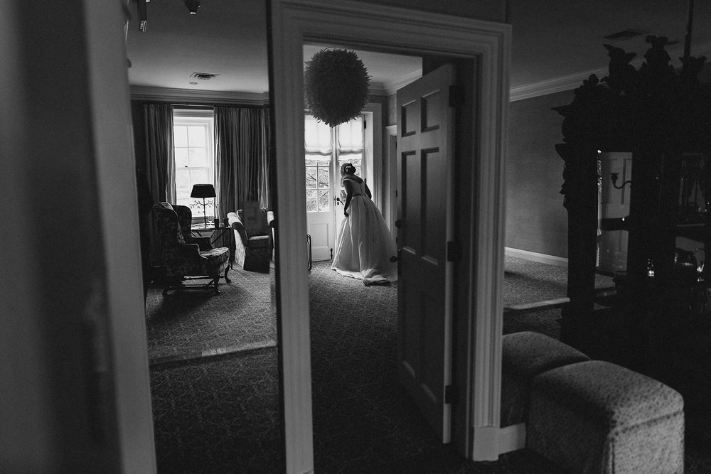 Graydon-Hall-Manor-Wedding-Toronto's-Best-Wedding-Photography-Ryanne-Hollies-Intimate-Small-Modern-Colourful-Wedding-Bride-Getting-Ready-Ferre-Sposa-Gown-bride-putting-wedding-dress-pre-wedding-ceremony-looking-at-guests.jpg
