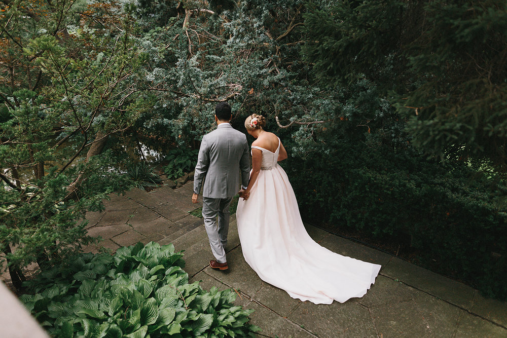 Graydon-Hall-Manor-Wedding-Toronto's-Best-Wedding-Photography-Ryanne-Hollies-Intimate-Small-Modern-Colourful-Wedding-candid-documentary-portraits-of-the-bride-and-groom-holding-hands-walking-through-forest-grounds.jpg
