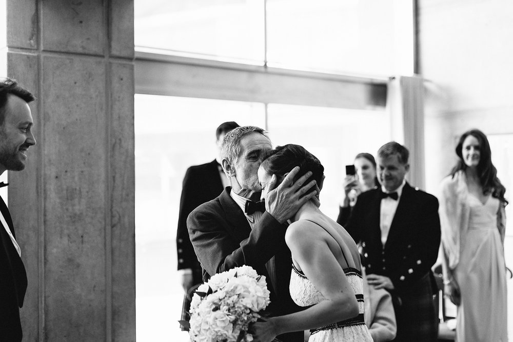 toronto-city-hall-elopement-wedding-old-city-hall-nathan-phillips-square-toronto-wedding-photographer-ryanne-hollies-photography-ceremony-city-hall-entrance-scotish-with-bagpipes-bride-and-father-emotional-candid.jpg