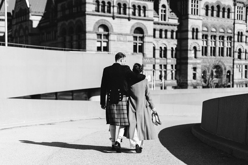 toronto-city-hall-elopement-wedding-old-city-hall-nathan-phillips-square-toronto-wedding-photographer-ryanne-hollies-photography-candid-documentary-portraits-of-bride-and-groom-walking-bw.jpg