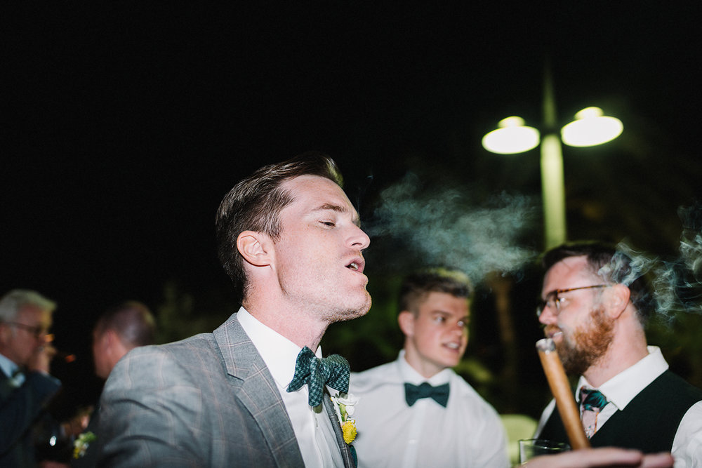 destination-wedding-photographer-from-toronto-ryanne-hollies-photography-documentary-editorial-style-toronto-wedding-photographer-junebug-weddings-reception-partying-candid-moments-grooman-groom-smoking-cigars-cool-hipster.jpg