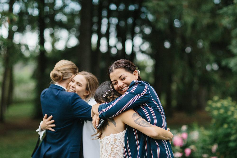 cambium-farms-wedding-ryanne-hollies-photography-gay-wedding-lgbtq-trendy-cool-badass-junebug-weddings-inspiration-cocktail-hour--candid-documentary-moments-brides-hugging-friends.jpg