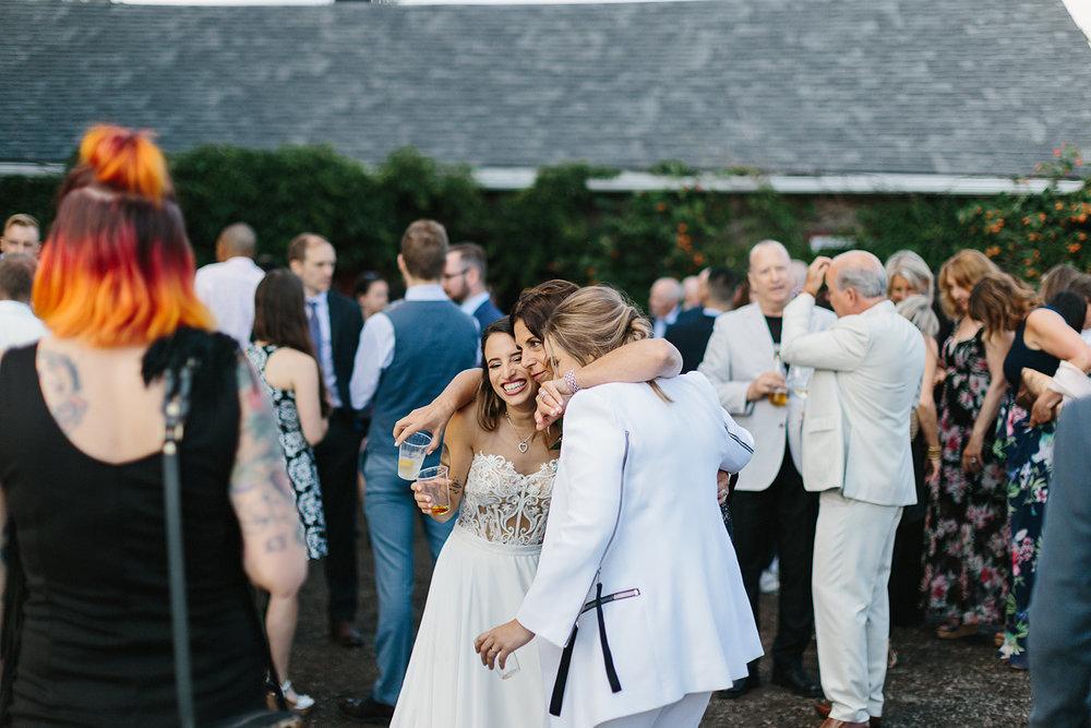 cambium-farms-wedding-ryanne-hollies-photography-gay-wedding-lgbtq-trendy-cool-badass-junebug-weddings-inspiration-cocktail-hour--candid-documentary-moments-bride-hugging-friendS.jpg