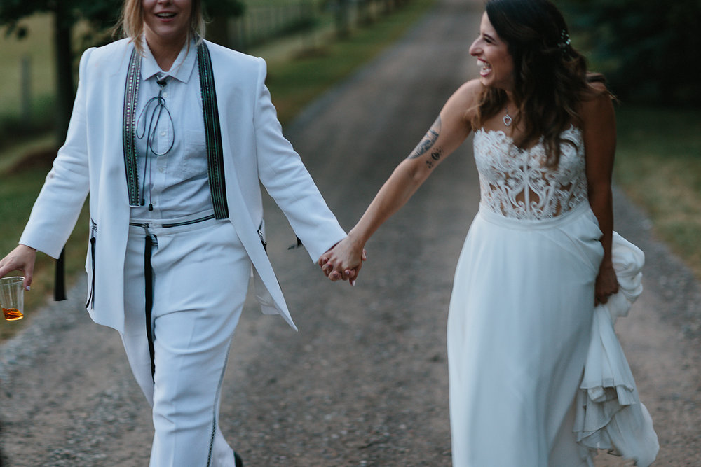cambium-farms-wedding-ryanne-hollies-photography-gay-wedding-lgbtq-trendy-cool-badass-junebug-weddings-inspiration-wedding-reception-in-a-barn-portraits-at-sunset-bride-and-bride-golden-hour-walking.jpg