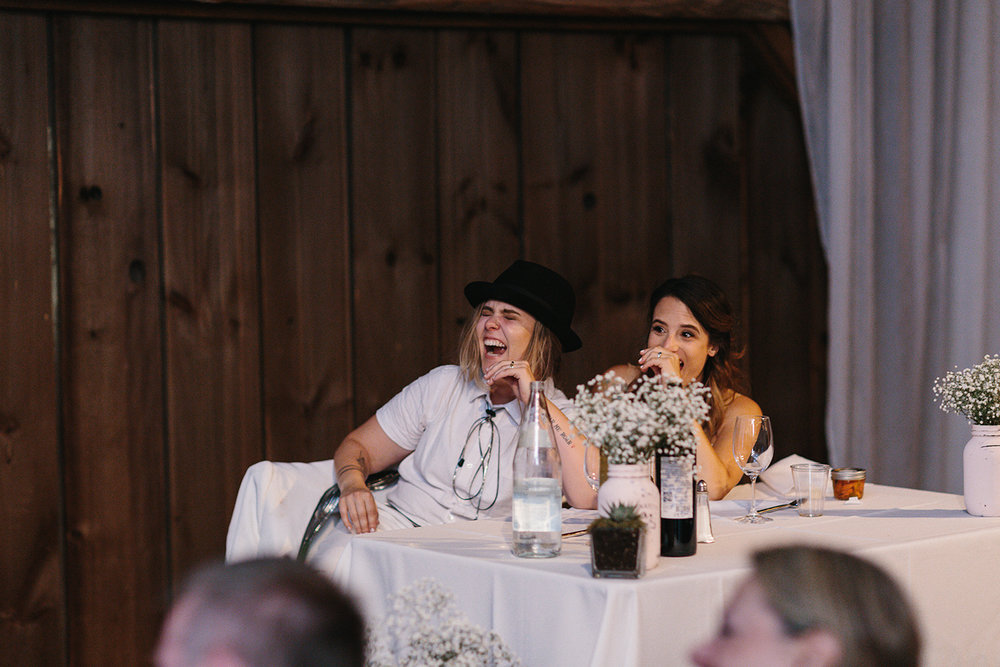 cambium-farms-ryanne-hollies-photography-gay-wedding-lgbtq-trendy-cool-badass-junebug-weddings-inspiration-wedding-reception-huge-party-candid-fun-moments-memories-brides-laughing-at-speeches-embarrassed-crying-laughing.jpg