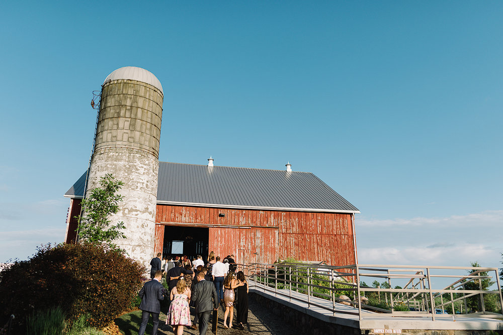 cambium-farms-wedding-ryanne-hollies-photography-gay-wedding-lgbtq-trendy-cool-badass-junebug-weddings-inspiration-cocktail-hour-bride-and-bride-with-guests-candid-entering-reception.jpg