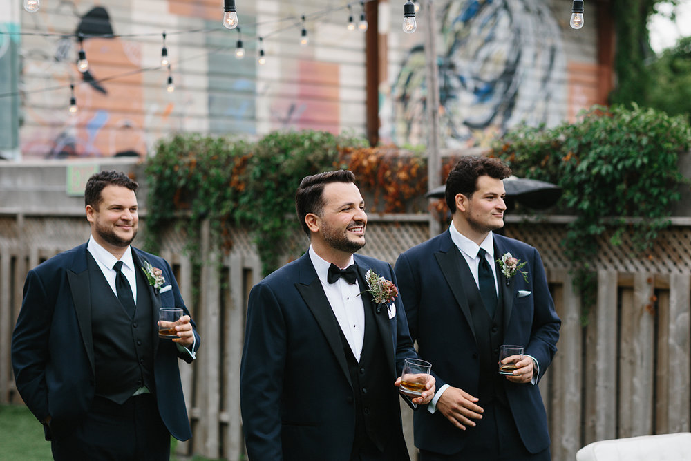 downtown-toronto-wedding-photographer-ryanne-hollies-photography-airship37-distillery-district-wedding-day-modern-minimalist-venues-in-toronto-cool-trendy-hipster-party-bus-outdoor-patio-graffiti-groom-and-groomsmen-greeting-guests.jpg