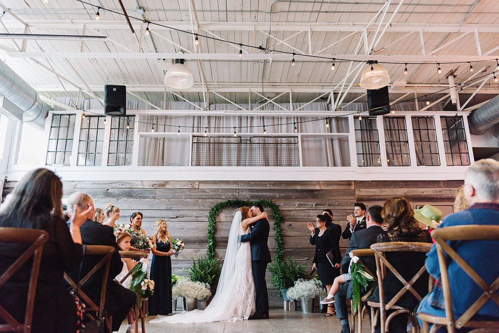 downtown-toronto-wedding-photographer-ryanne-hollies-photography-airship37-distillery-district-wedding-day-modern-minimalist-venues-in-toronto-ceremony-documentary-moments-bride-and-groom-first-kiss-epic.jpg
