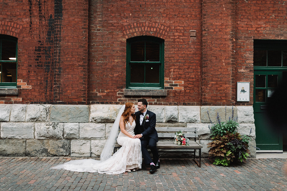 wedding-photographers-ryanne-hollies-photography-photojournalism-artistic-moody-toronto-airship37-distillery-district-groom-and-bride-poratraits-intimate-authentic-film-analog-photography-artistic-moody-editorial-magazine-sitting-on-bench.jpg