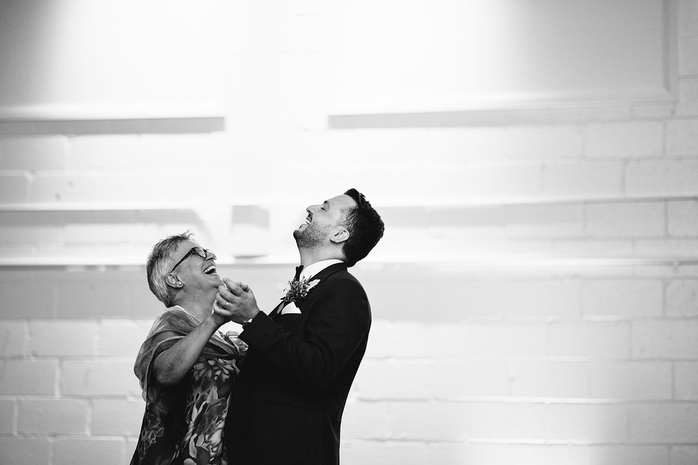 torontos-best-wedding-photographers-ryanne-hollies-photography-photojournalism-artistic-moody-toronto-airship37-graffiti-editorial-reception-mother-son-dance-with-groom-so-cute-laughing.jpg