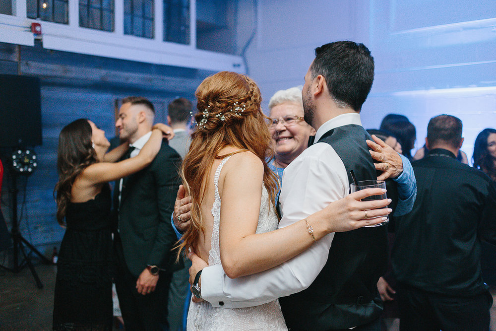 torontos-best-wedding-photographers-ryanne-hollies-photography-photojournalism-artistic-moody-toronto-airship37-graffiti-editorial-reception-dancing-together-hilarious-good-times-memories-bride-and-groom-with-grandma-sweet-hugging.jpg