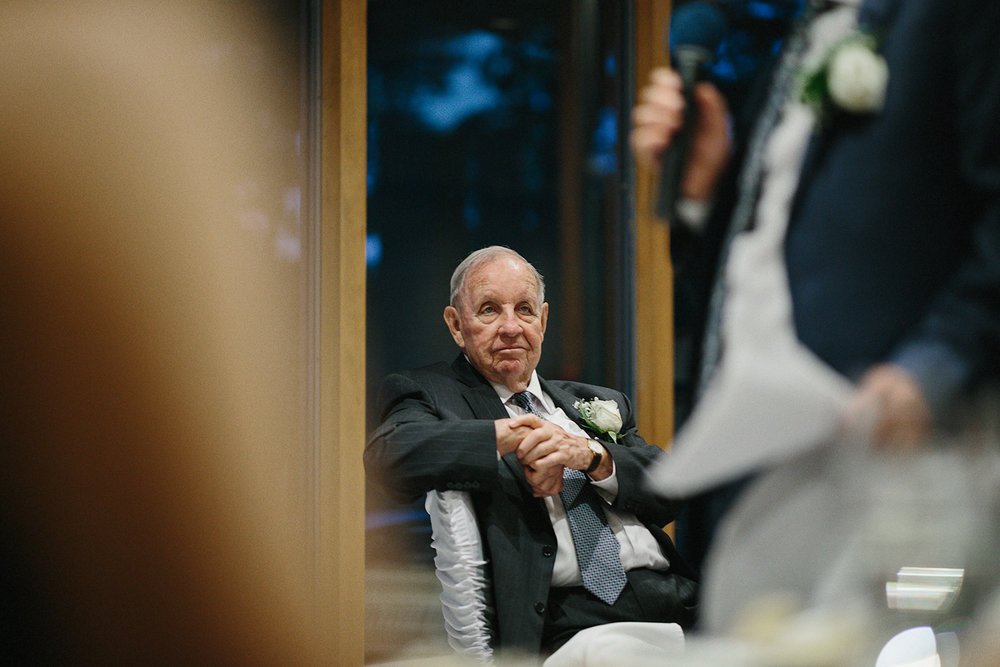hidden-valley-resort-film-photography-torontos-best-wedding-photographers-ryanne-hollies-photography-calgary-muskoka-haliburton-port-carling-cottage-wedding-at-resort-party-candid-documentary-photography-speeches-grandpa-listening.jpg