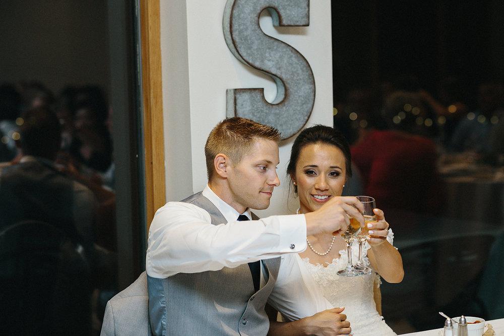 hidden-valley-resort-film-photography-torontos-best-wedding-photographers-ryanne-hollies-photography-calgary-muskoka-haliburton-port-carling-cottage-wedding-at-resort-party-candid-documentary-photography-speeches-bride-and-groom-cheers.jpg