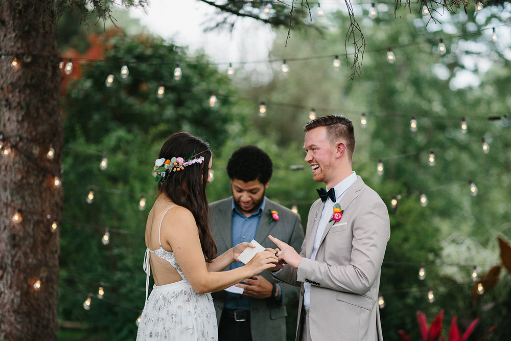 Backyard-family-intimate-cottage-wedding-chatum-kent-toronto-ontario-film-photographer-ryanne-hollies-photography-diy-string-lights-ceremony-space-lanterns-groom-and-bride-ring-exchange-emotional-smiles-cool-trendy-hipster-groom-laughing.jpg
