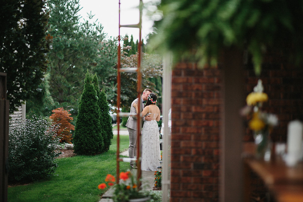 Backyard-family-intimate-cottage-wedding-chatum-kent-toronto-ontario-film-photographer-ryanne-hollies-photography-diy-string-lights-ceremony-space-lanterns-groom-and-bride-just-married-biodegradable-confetti-walking-away-kiss.jpg