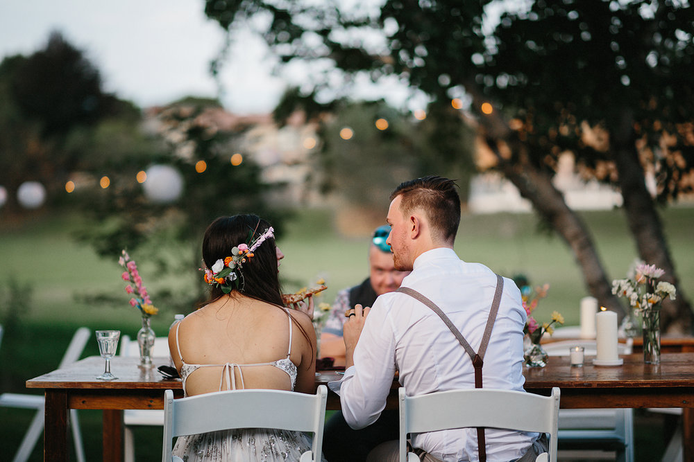 Backyard-toronto-film-photographer-ryanne-hollies-photography-diy-string-lights-and-lanterns-reception-dinner-documentary-wooden-harvest-tables-diy-decor-speeches-bride-and-groom-eating-pizza-for-dinner.jpg