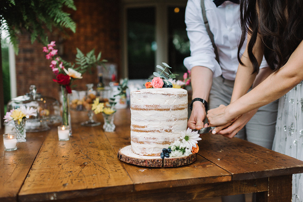Backyard-toronto-film-photographer-ryanne-hollies-photography-diy-string-lights-and-lanterns-reception-dinner-documentary-wooden-harvest-tables-naked-cake-made-by-mom-cutting.jpg