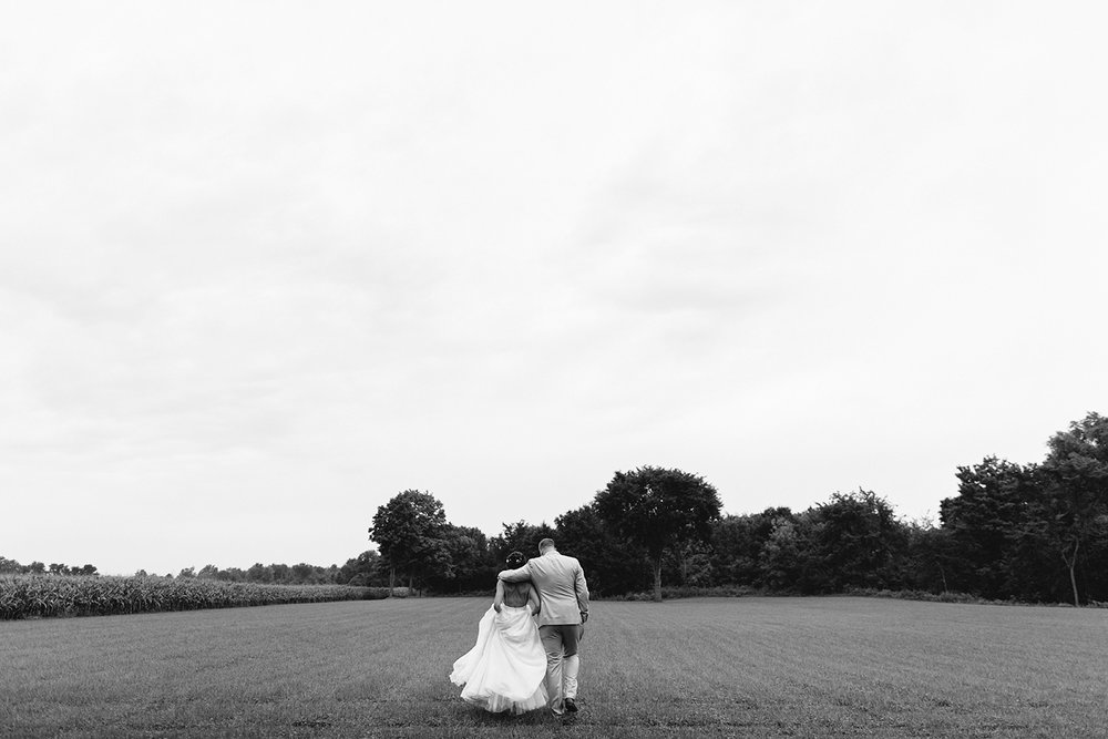 Alternative-Toronto-Wedding-Photographers-Photojournalistic-Wedding-Photography-in-Toronto-bradford-barn-farm-wedding-venue-rustic-inspiration-bride-and-groom-couples-portraits-in-corn-field-walking-away-cinematic.jpg