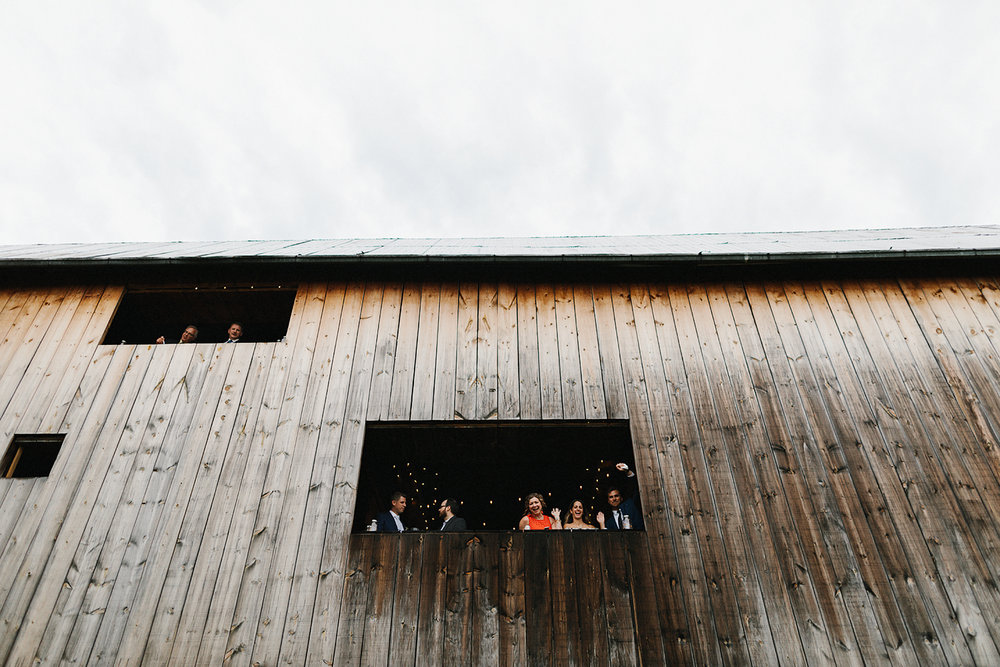 Alternative-Toronto-Wedding-Photographers-Photojournalistic-Wedding-Photography-in-Toronto-bradford-barn-farm-wedding-venue-rustic-inspiration-bride-and-groom-couples-portraits-in-barn-guests-watching-funny-waving.jpg