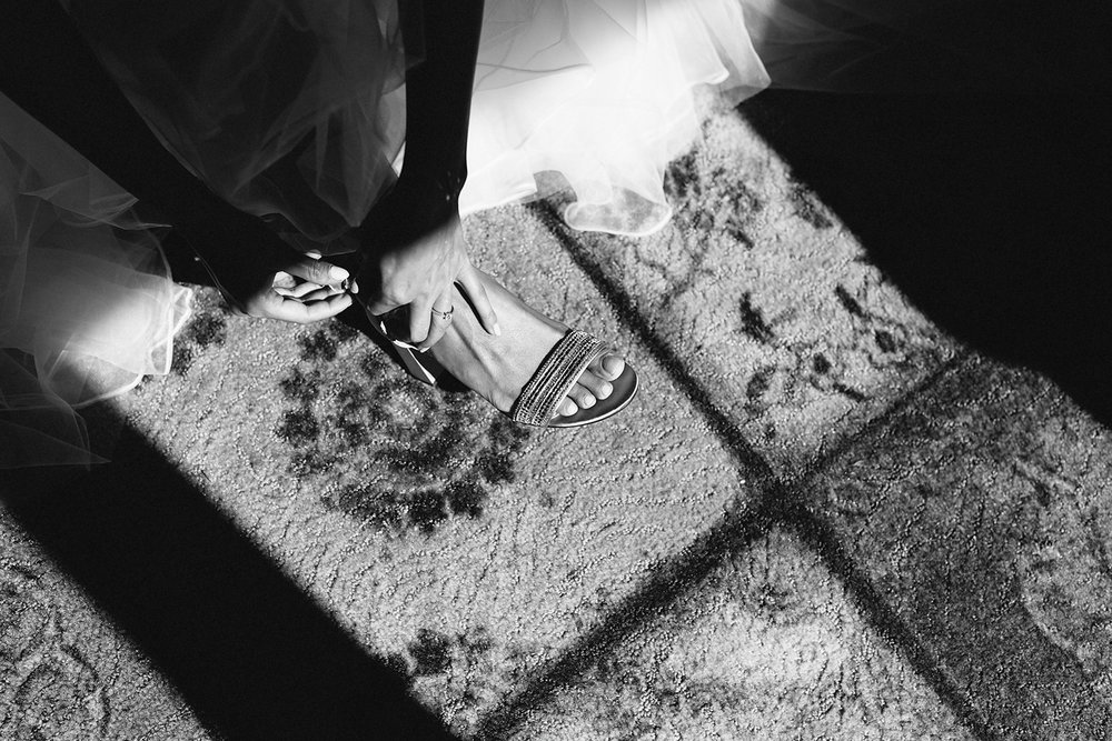 Bride-putting-on-shoes-At-Egaridge-Resort-Venue-Muskoka-Ontario.jpg