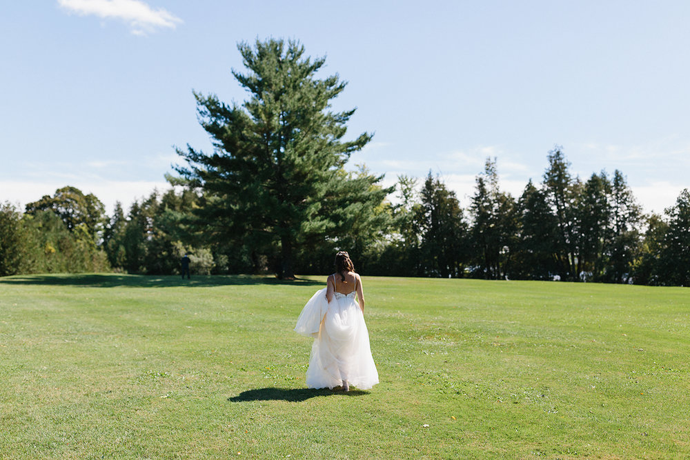 Bride-walking-up-to-groom-from-far-away-for-first-look-At-Eganridge-Resort-Venue-Muskoka-Ontario.jpg