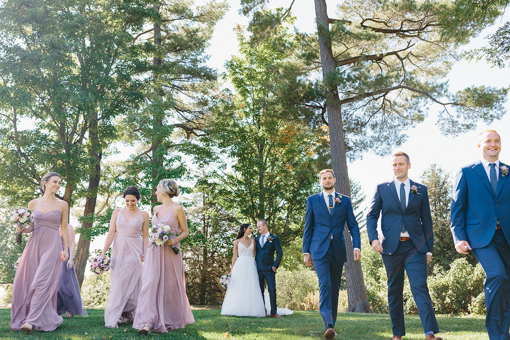 Bridal-Party-walking-framing-couple-together-At-Egaridge-Resort-Venue-Muskoka-Ontario-Wedding-Photography-by-Ryanne-Hollies-Photography-Toronto-Documentary-Wedding-Photographer.jpg
