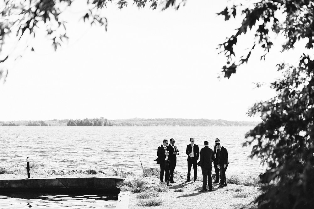 groomsmen-drinking-beer-by-the-lake-At-Egaridge-Resort-Venue-Muskoka-Ontario-Wedding-Photography-by-Ryanne-Hollies-Photography-Toronto-Documentary-Wedding-Photographer.jpg