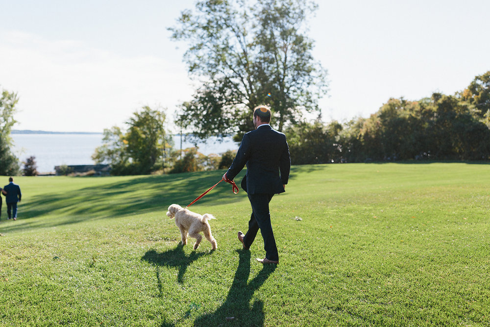 ceremony-dog-walking-down-with-groomsman-At-Egaridge-Resort-Venue-Muskoka-Ontario-Wedding-Photography-by-Ryanne-Hollies-Photography-Toronto-Documentary-Wedding-Photographer.jpg