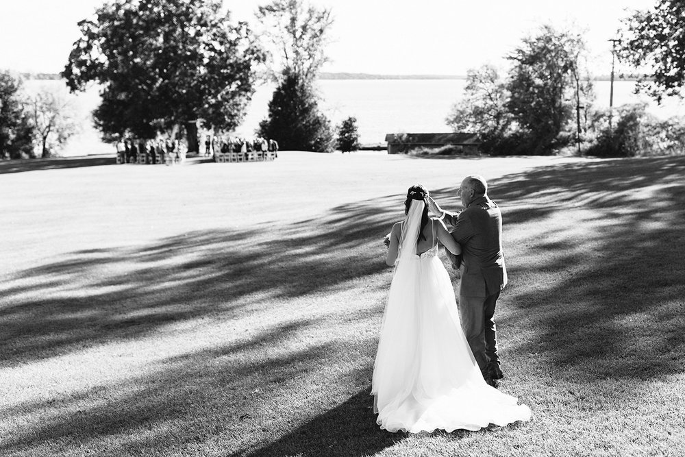 ceremony-bride-walking-down-the-aisle-with-dad-wiping-away-tears-At-Egaridge-Resort-Venue-Muskoka-Ontario-Wedding-Photography-by-Ryanne-Hollies-Photography-Toronto-Documentary-Wedding-Photographer.jpg