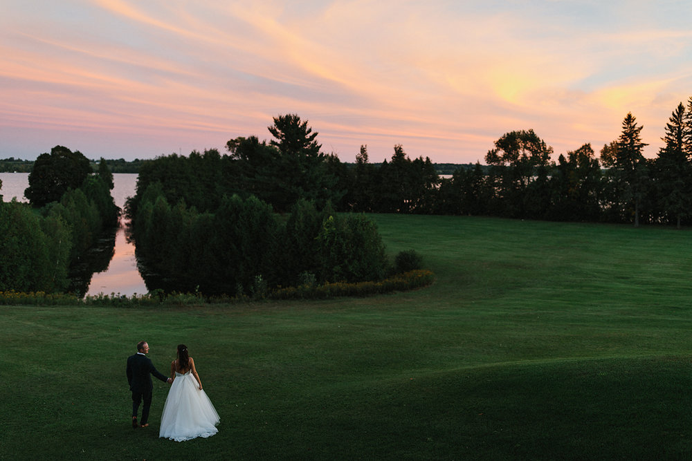 sunset-golden-hour-bride-and-groom-in-field-lakeside-At-Eganridge-Resort-Venue-Muskoka-Ontario-Wedding-Photography-by-Ryanne-Hollies-Photography-Toronto-Documentary-Wedding-Photographer.jpg