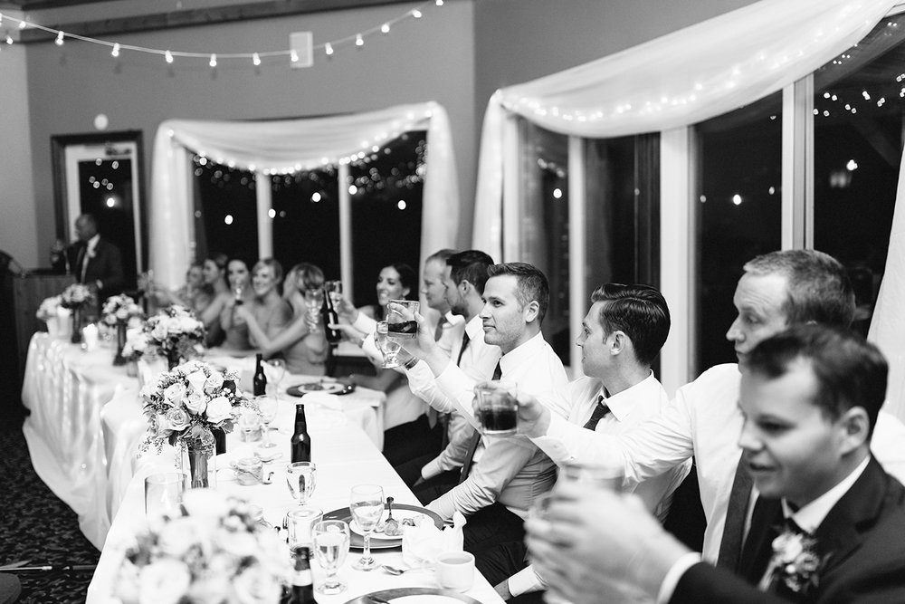 head-table-cheers-toast-glasses-during-reception-At-Eganridge-Resort-Venue-Muskoka-Ontario-Wedding-Photography-by-Ryanne-Hollies-Photography-Toronto-Documentary-Wedding-Photographer.jpg
