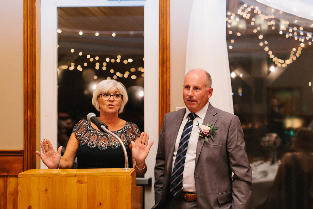 brides-parents-speech-sweet-moments-with-glasses-during-reception-At-Eganridge-Resort-Venue-Muskoka-Ontario-Wedding-Photography-by-Ryanne-Hollies-Photography-Toronto-Documentary-Wedding-Photographer.jpg
