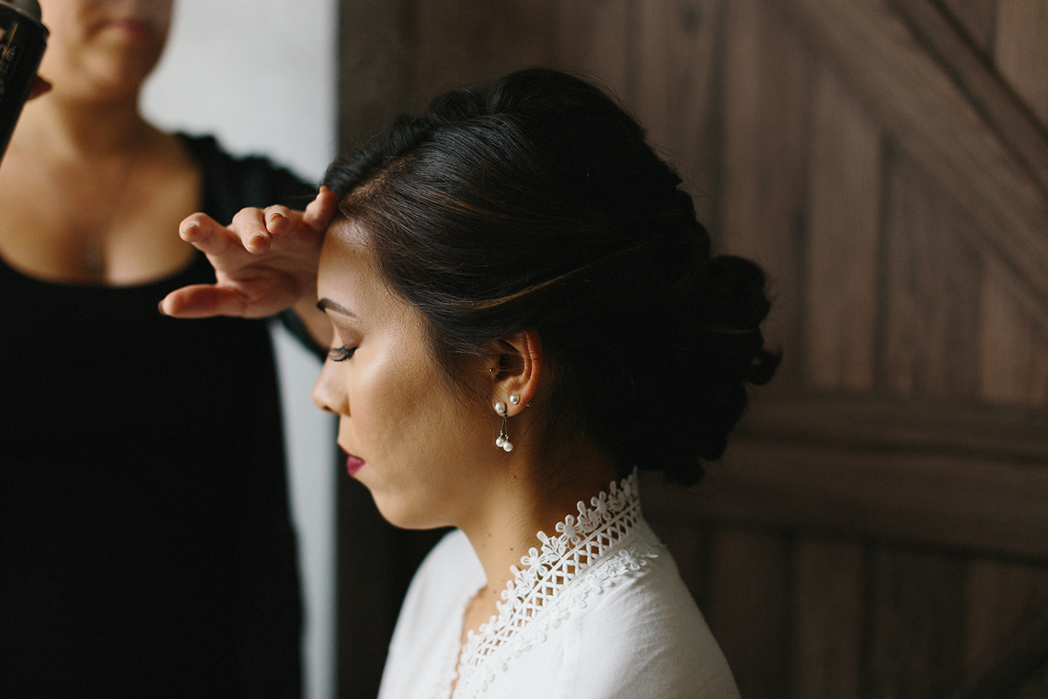 bride-getting-makeup-done-in-white-bridal-robe-