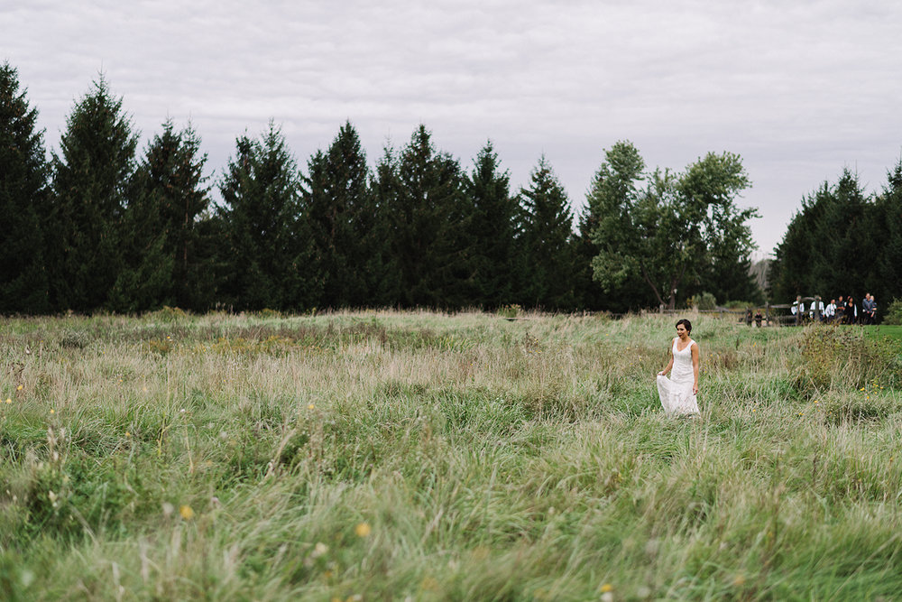 bellamere-winery-cottage-first-look-bride-walking-up-bridal-party-watching-epic-cinetmatic-best-torontos-wedding-photographers-candid-documentary-style-photography-london-ontario-winery-wedding-inspiration.jpg