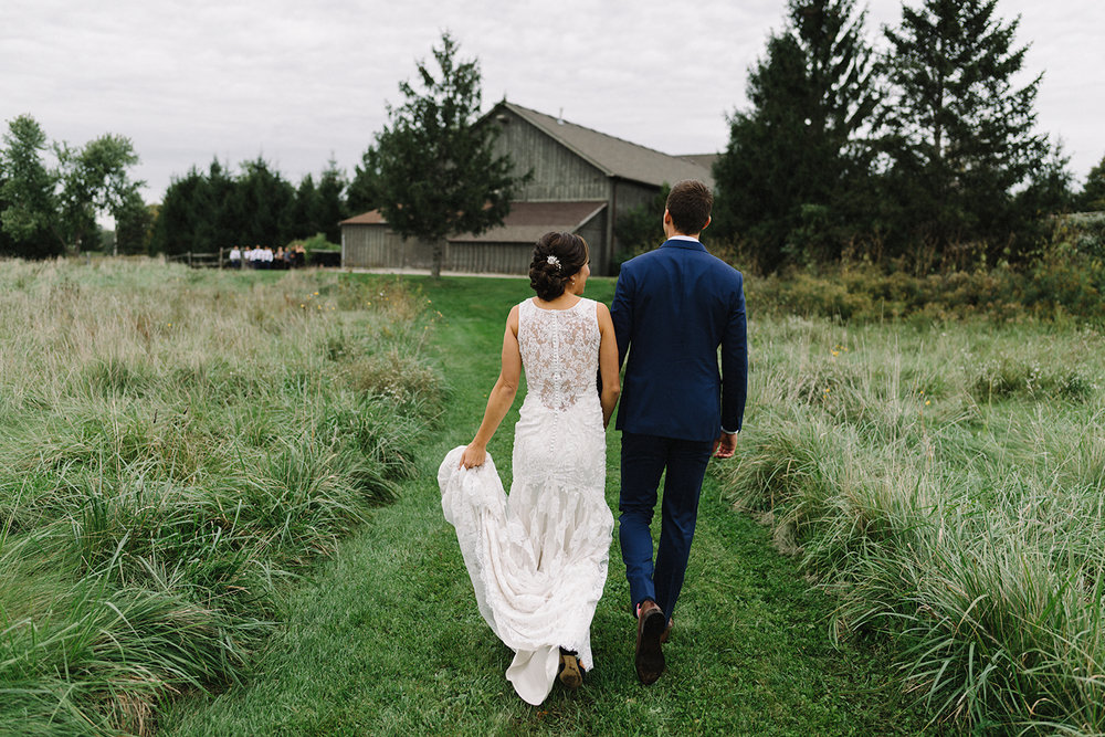 bellamere-london-venue-first-look-bride-and-groom-walking-away-in-field-cinetmatic-best-torontos-wedding-photographers-candid-documentary-style-photography-london-ontario-winery-wedding-inspiration.jpg