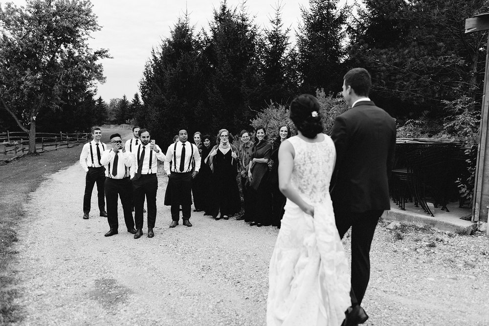 bellamere-london-venue-first-look-bride-and-groom-walking-to-bridal-party-best-torontos-wedding-photographers-candid-documentary-style-photography-london-ontario-winery-wedding-inspiration.jpg