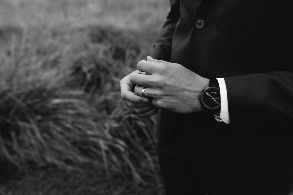 bw-groom-hands-portrait-in-field-wilderness-outdoors-romantic-moody-real-moments-photos-toronto's-best-wedding-photographers-candid-documentary-style-photography-london-ontario-winery-wedding-inspiration.jpg