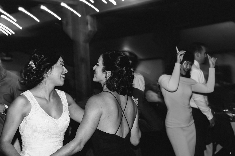 bw-candid-bride-and-sister-dancing-in-barn-with-string-lights-toronto's-best-analog-documentary-wedding-photographers-candid-photography-london-ontario-wedding-inspiration.jpg