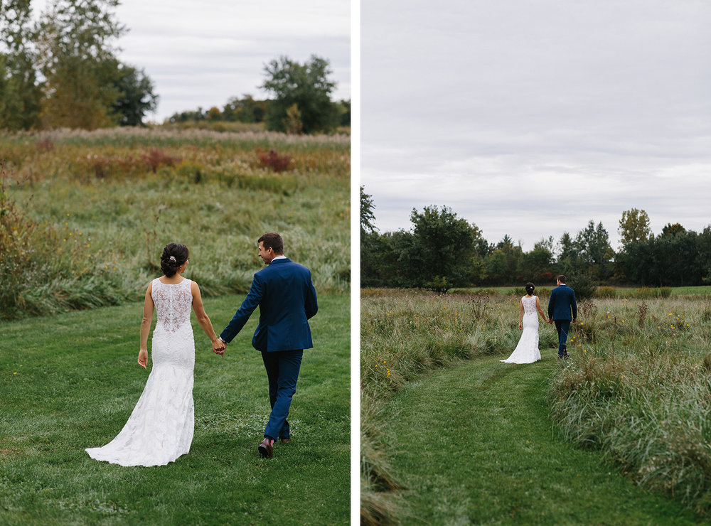 1-bride-and-groom-portraits-walking-in-a-field-romantic-moody-real-moments-at-bellamere-winery-toronto's-best-wedding-photographers-candid-documentary-style-photography-london-ontario-winery-wedding-inspiration.jpg