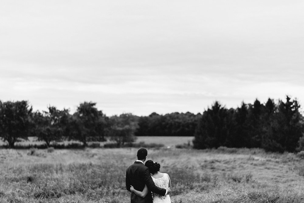 bw-bride-and-groom-portraits-in-field-hugging-cinematic-romantic-moody-real-moments-at-bellamere-winery-toronto's-best-wedding-photographers-candid-documentary-style-photography-london-ontario-winery-wedding-inspiration.jpg