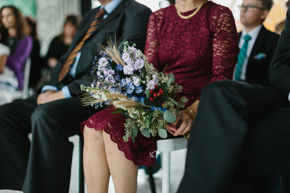 Prince-Edward-County-Wedding-Photographer-Drake-Devonshire-Elopement-Ryanne-Hollies-Photography-junebug-weddings-best-of-the-best-2018-ceremony-bride-and-groom-guests-holding-bouquet.jpg