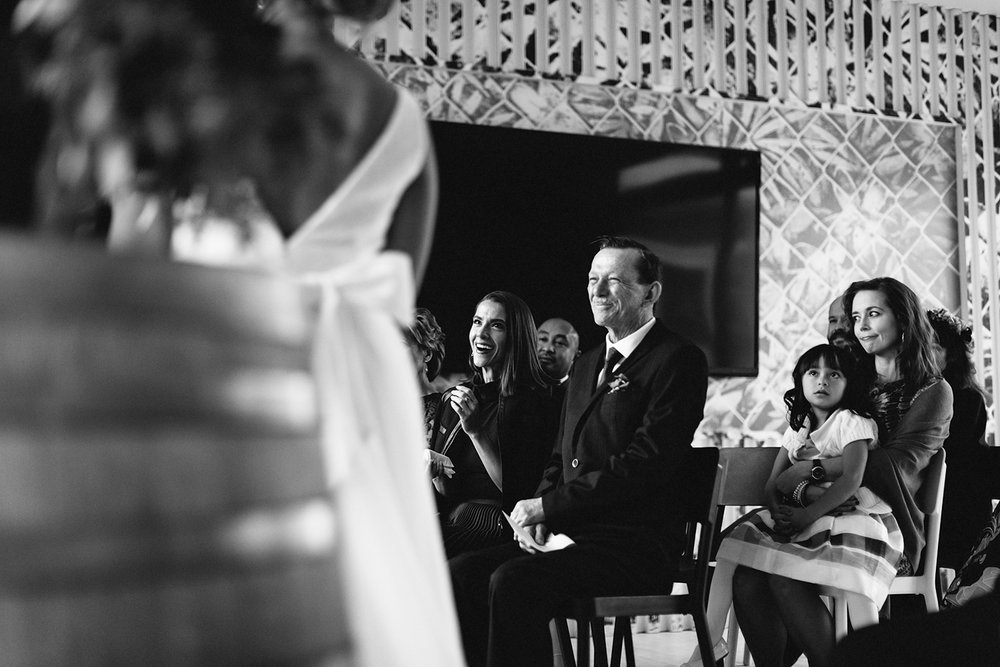 Prince-Edward-County-Wedding-Photographer-Drake-Devonshire-Elopement-Ryanne-Hollies-Photography-junebug-weddings-best-of-the-best-2018-ceremony-bride-and-groom-guests-laughing-bw.jpg