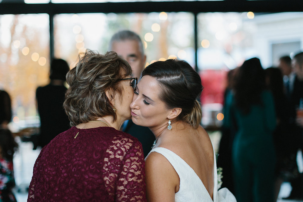 Prince-Edward-County-Wedding-Photographer-Drake-Devonshire-Elopement-Ryanne-Hollies-Photography-junebug-weddings-best-of-the-best-2018-cocktail-hour-mom-and-bride-kiss.jpg