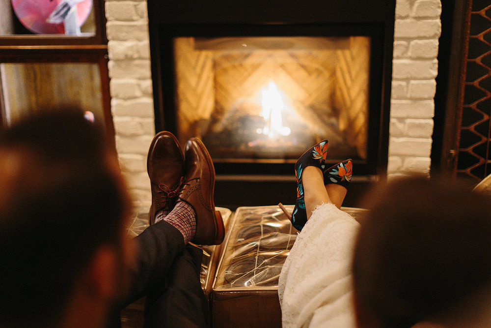 Prince-Edward-County-Wedding-Photographer-Drake-Devonshire-Elopement-Ryanne-Hollies-Photography-junebug-weddings-best-of-the-best-reception-groom-and-bride-at-fireplace-feet-cute.jpg