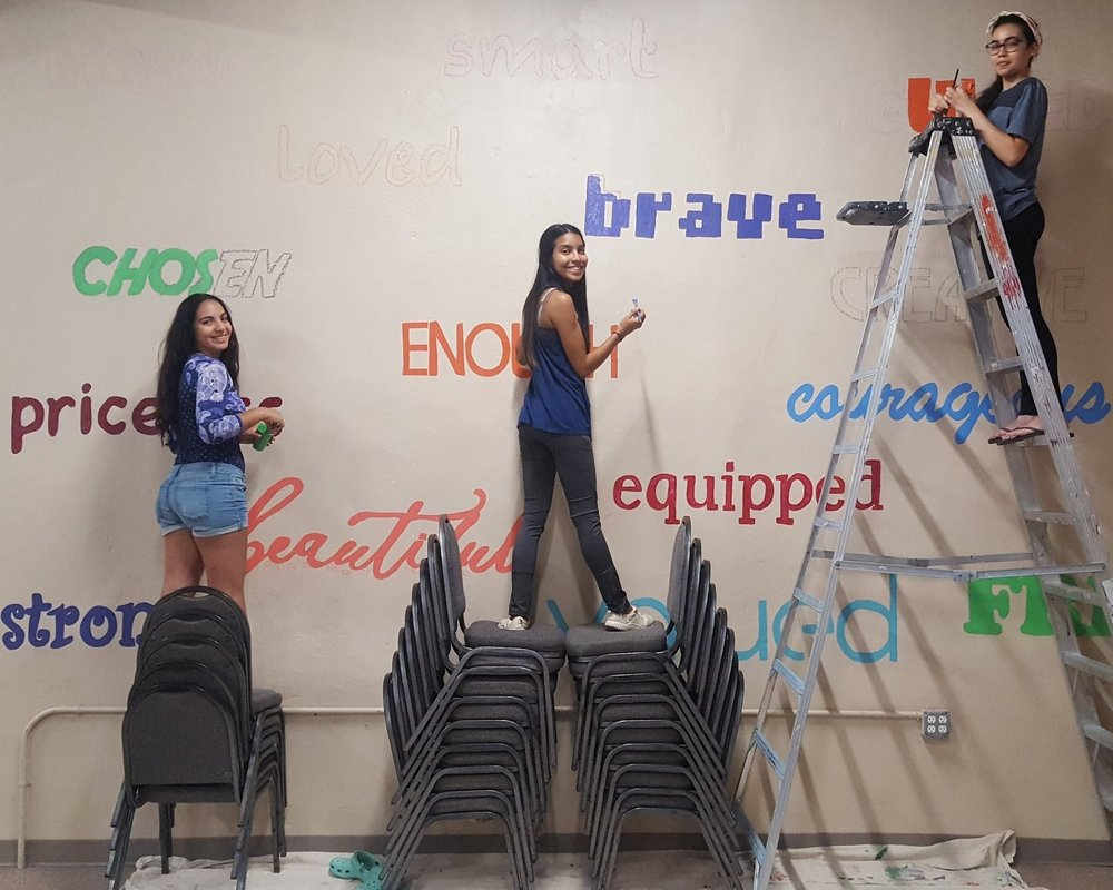 Anelys on the chairs in the middle, along with fellow interns, painting a mural at the City Light Ministry where they served children from the Reading community